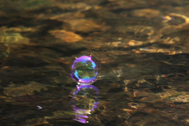 A child's soap bubble glistens as it floats down a river.
