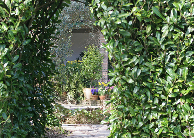 Concealed by brick walls and hedges is another private garden with a covered porch and fountain.