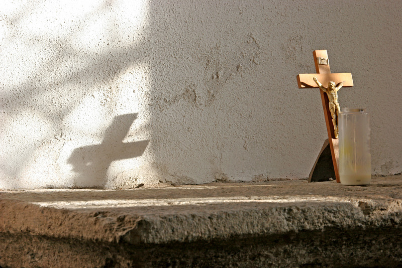 Afternoon sunshine and the cross on the wall of a small side chapel.