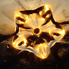 "Kidzmom - ""Sundown: The hour of descent for our shining star""<br /> <br /> Distortion achieved via a shoot through with a 2L clear plastic Coca Cola bottle (spout cut off). The star formation results from the bend at the bottom of the 2L container. I also scratched up the feet of the bottle for effect (on rough concrete). This sunset was also shot through a pane of dirty/smudged glass for further distortion."