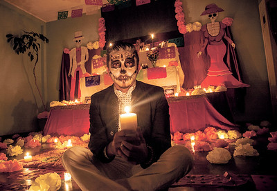 Jaime Gonzalez, a spiritual leader for the youth group Totus Tuus, poses in front of their Dia de los Muertos alter at the end of their celebration  on Friday November 3, 2017 at Our Lady of Guadalupe Church. Gabriela Campos/The New Mexican