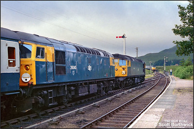 26015 is detached from 2K02 0655 Inverness-Kyle of Lochalsh at Achnasheen on 21/07/1983 and runs forward onto 26044 (visible in the distance) which was running low on coolant whilst working 2N12 0710 Kyle of Lochalsh-Inverness. Inverness TMD had been made aware of 26044's plight and hastilly attached 26015 to the front of 2K02 prior to departure. 26040 continued to Kyle of Lochalsh with 2K02 whilst 26015 piloted 26044 to Inverness on 2N12.