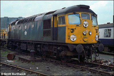 Dumped outside in the yard at St Rollox works, 26045 shows signs of fire damage on 24/07/1983.