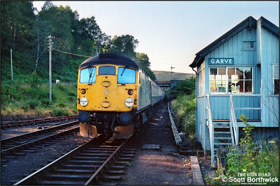 26034 approaches Garve on 21/07/1983 whilst working 2N35 1710 Kyle of Lochalsh-Inverness.