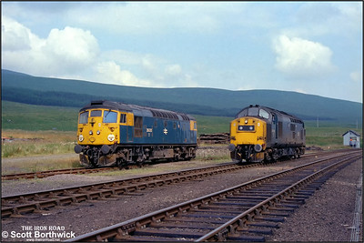 Rescue for 2N20 1110 Kyle of Lochalsh-Inverness arrives some two hours later in the shape of 37183 seen passing the stricken 26035 at Achnasheen on 25/07/1983.