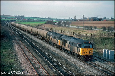 Filthy 31319+31199 are held at the signal at Melton Ross whilst working 6D42 0934 Leeds ORT-Lindsey Oil Refinery on 06/03/1992.