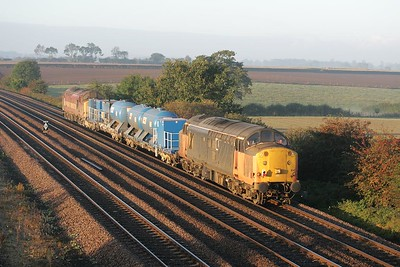 37516 and 37503 are illuminated by early morning autumnal sunshine at Bolton Percy as they work 6T82 0634 Knaresborough-York water cannon on 09/10/2004.