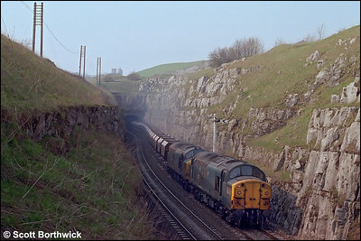 37047+37211 blast out of Dove Holes tunnel and into the cutting whilst in charge of the empties from Hope Street (Salford)-Peak Forest South SS on 23/04/1987.