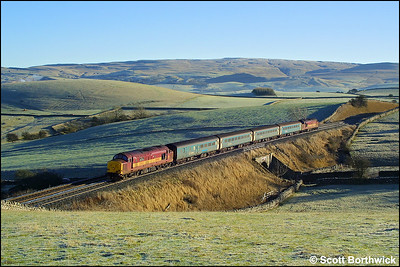 With the weak winter sun having little impact on the overnight frost at Waitby, 37411 leads 37408 whilst working 1M53 0947 Leeds-Carlisle on 29/12/2003. And for those of you that were there, yes I have 'removed' the red car that was parked under the bridge to the disgust of us all !!