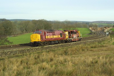 Trundling along the Tyne Valley line at Upper Denton, 37893 is pictured working 7Z13 0815 Forth CE Sdgs-Carlisle NY on 28/11/2003.