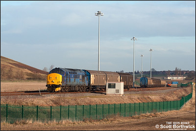 37203 departs from the exchange sdgs at Birch Coppice on 24/01/2005 with 6G42 1123 Birch Coppice-Bescot Yard. 'Enterprise' trip with empty vans that had conveyed automotive parts to the Volkswagen national parts distribution centre located at the Birch Coppice Business Park, Dordon, Warwickshire.. TNT's Unimog can be seen in the distance. This vehicle moves the vans between the exchange sdgs and the warehouse facility at Birch Coppice.