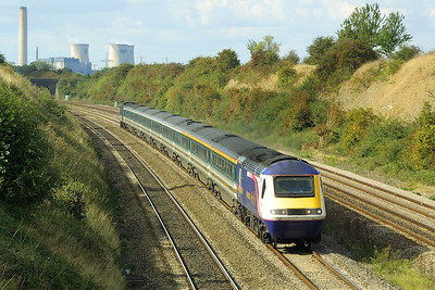 With Didcot power station dominating the background, an unidentified First Great Western HST speeds through South Moreton cutting on 24/09/2002 with a London Paddington bound express.