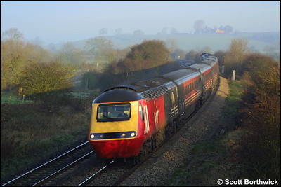 An unidentified Virgin HST speeds through the early morning mist at Holmes House Farm, Bishops Itchington with a southbound Cross Country service on 06/12/2001.
