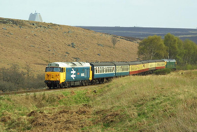 50033 heads the 1520 Pickering-Grosmont service at Moorgates on 24/04/2004. 50007 is on the rear. RAF Fylingdales nuclear missile early warning station is prominent on the hillside.