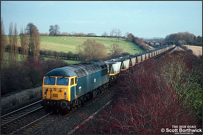 56026 powers up the Sharnbrook bank at Souldrop with 6M04 1045 TuThO Brookgate Sdgs-Toton North Yard on 27/11/1990.