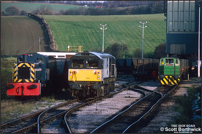 58024 has detached from its train of empty HAA hoppers at Oxcroft Opencast Disposal Point on 19/11/1992 and is in the process of running round its train in order to reverse onto the hoppers being drawn through the loader by the sites Hunslet industrial shunting locomotive. 03037 also in industrial use stands to the left of 58024. Oxcroft closed in 2006, along with the disappearance of mines in Derbyshire. It was briefly reopened by UK Coal when they started a coal recovery operation in 2007 to sift through nearby pit tips and recover around 14000 tonnes of coal. It closed again shortly after and is now flattened and all track lifted.