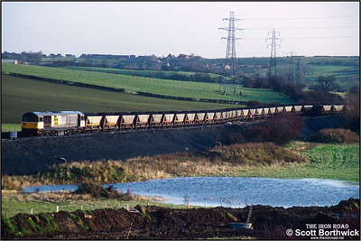 58024 departs from Oxcroft Opencast Disposal Point on 19/11/1992 with a 'merry go round' coal train. Oxcroft closed in 2006, along with the disappearance of mines in Derbyshire. It was briefly reopened by UK Coal when they started a coal recovery operation in 2007 to sift through nearby pit tips and recover around 14000 tonnes of coal. It closed again shortly after and is now flattened and all track lifted.
