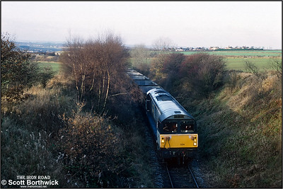 58024 traverses the short branch from Oxcroft Colliery Branch Jnct down to Oxcroft Opencast Disposal Point with a rake of empty HAA 'merry go round' coal hoppers for loading on 19/11/1992. Oxcroft closed in 2006, along with the disappearance of mines in Derbyshire. It was briefly reopened by UK Coal when they started a coal recovery operation in 2007 to sift through nearby pit tips and recover around 14000 tonnes of coal. It closed again shortly after and is now flattened and all track lifted.