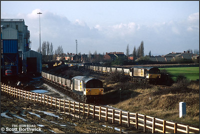 58047 'Manton Colliery' draws 6G42 Kiveton Colliery-West Burton Power Station forward as loading is almost complete whilst 58018 'High Marnham Power Station passes with an Oxcroft Opencast Disposal Point-Cottam Power Station train at Kiveton Colliery on 19/11/1992. The last shift worked in September 1994. A skeleton workforce along with contractors remained to close and demolish the colliery after almost 130 years of production. In 1995 the headgear was pulled down.