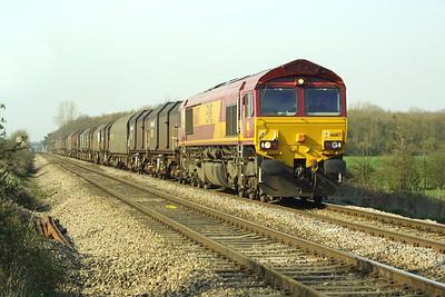 66187 hauls 6V07 1400 Round Oak-Llanwern steel empties at Pirton Crossing on 26/03/2002.