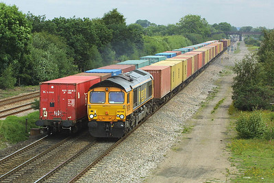 Container trains pass at North Stafford Jnct on 24/07/2004. 66709 heads 4M21 0543 Felixstowe North FLT-Hams Hall as it passes a diverted 4L93 0822 Trafford Park-Ipswich Yard headed by 66501.