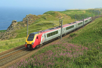 221111 skirts the Berwickshire coastline at Lamberton on 14/07/2003 as it heads for Edinburgh Waverley.