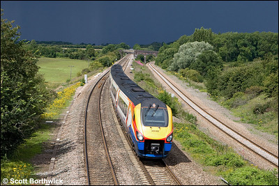 With Wellingborough getting a soaking in the distance, 222022 glides down Sharnbrook bank at Souldrop whilst forming the 1P39 1215 Corby-London St Pancras International on 24/07/2009.