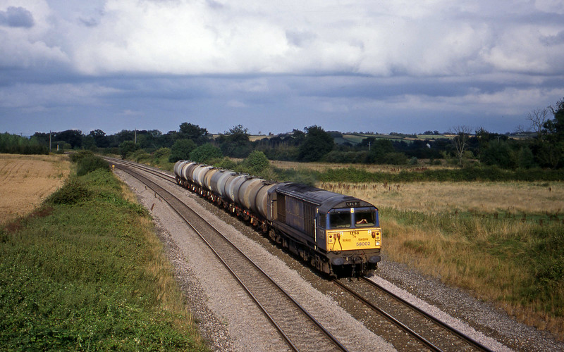 58002, 17.03 Westbury-Plymouth Tavistock Junction Yard, Creech St Michael, near Taunton, 9-8-99. Note 'headboard'.