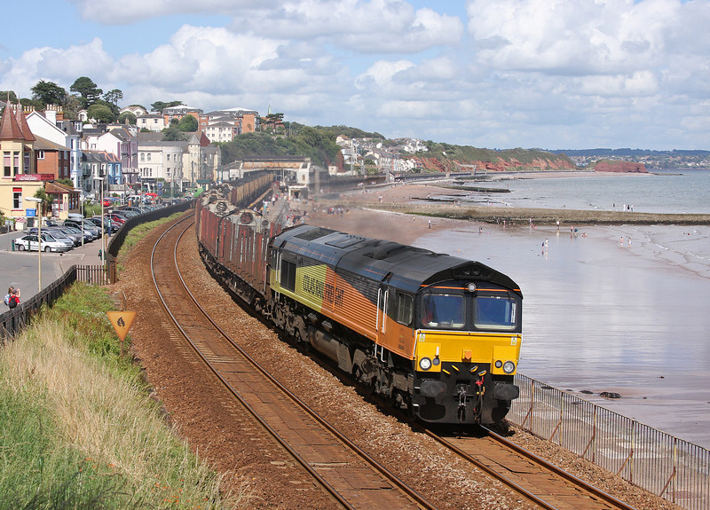 The driver of Class 66 No 66846 blasts a warning as it accelerates along Marine Parade, Dawlish, and approaches Kennaway Tunnel on the last few miles of its journey with the 08.11 Chirk Kronospan-Teigngrace empty timber carriers on 22-8-12.