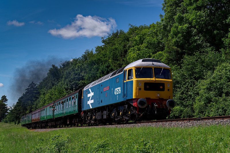 47579 exits the pine trees with the 11:35 Alresford - Alton, during the Diesel Gala <br /> on 3rd June 2018.