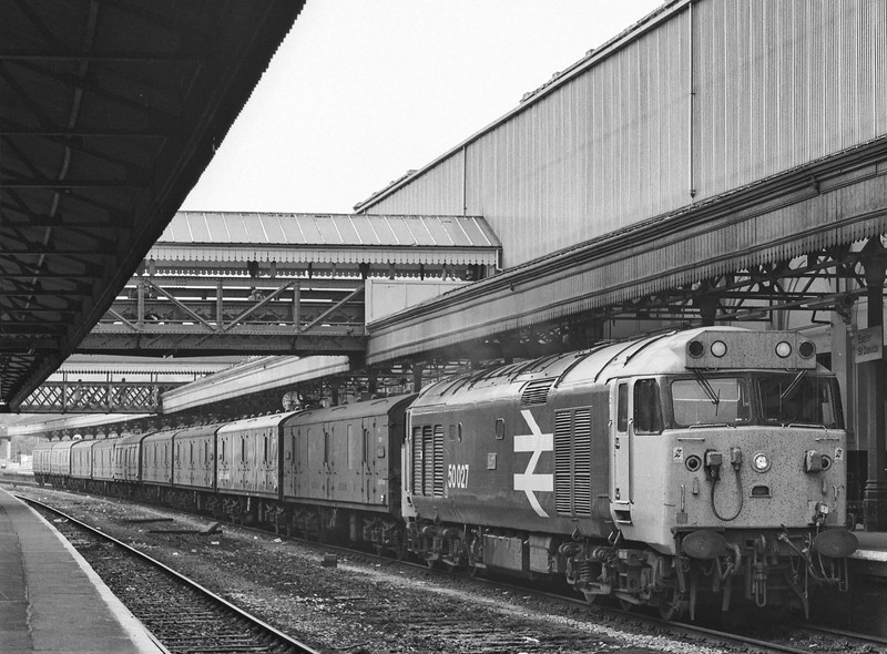 50027 at Exeter St Davids, with the 17:20 Paddington - Plymouth vans, on 18th May 1985. Scanned Negative.