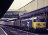 50027 at Exeter St Davids, with the 17:20 Paddington - Plymouth vans, on 18th May 1985. Scanned Transparency.