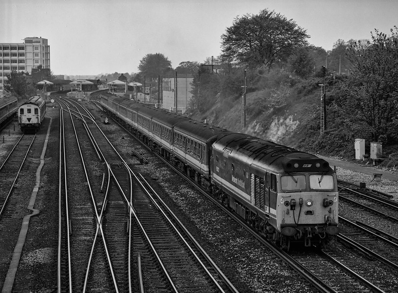 50027 departs from Basingstoke, with the 12:25 Exeter St Davids - Waterloo, <br /> on 11th May 1991. 205033 is stabled in the Long Valley siding. Scanned Negative.