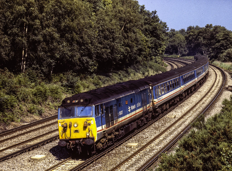 50027 rounding the curve at Pirbright, with 1V15, the 15:15 Waterloo - Exeter St Davids, <br /> on 22nd June 1990. Scanned Transparency.