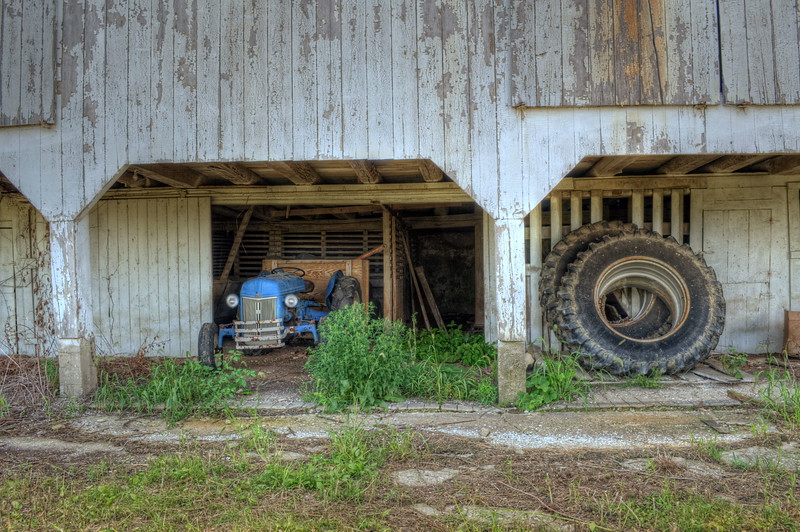 Old Blue  tractor resting in the barn .