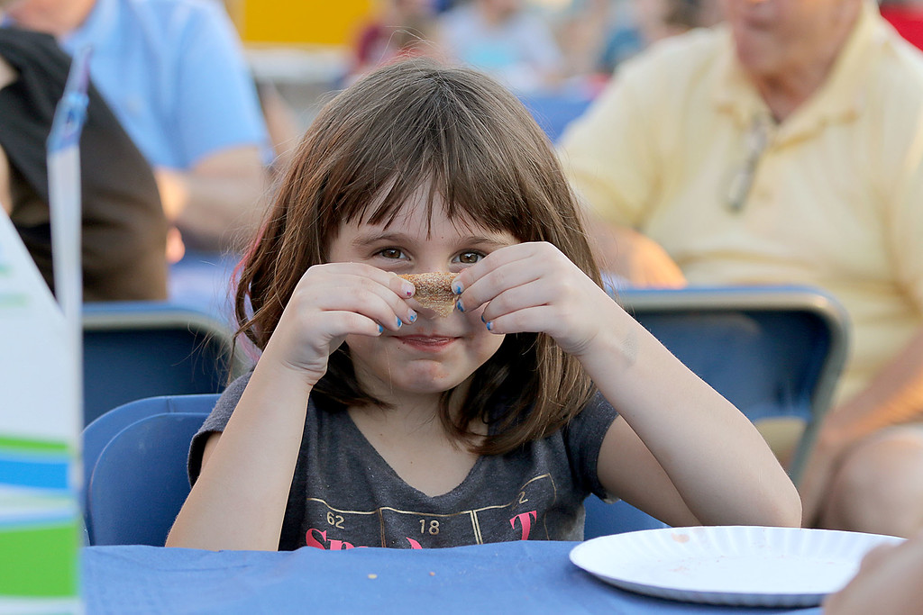 ". Leominster held its first-ever ""Dining Under The Stars!\"" event on Wednesday night. They closed down Central Street in Downtown Leominster and brought the restaurants and bars within the road closure out into the street for all to enjoy. Maddie Perla, 6, eats some pizza on the street as she and her family enjoy the festivities. SENTINEL & ENTERPRISE/JOHN LOVEa"