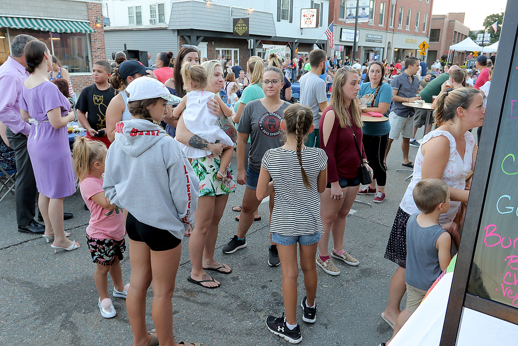 ". Leominster held its first-ever ""Dining Under The Stars!\"" event on Wednesday night. They closed down Central Street in Downtown Leominster and brought the restaurants and bars within the road closure out into the street for all to enjoy. many lined up to get some food from Mezcal during the eventl. SENTINEL & ENTERPRISE/JOHN LOVE"