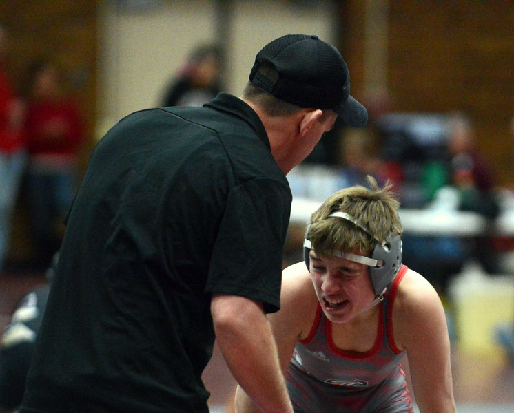 Loveland coach Troy Lussenhop checks on wrestler Cody Thompson after Thompson took a finger to his eye in his 113-pound semifinal match at Saturday's Diny Pickert Invitational wrestling tournament in Berthoud. (Mike Brohard/Loveland Reporter-Herald)