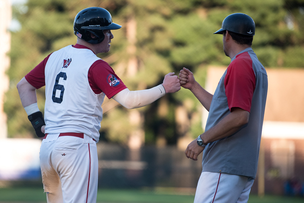 . Dirt Dawgs baserunner Zack Tower pounds the fist of third base coach during game 1 of the Futures League playoffs where the Wachusett Dirt Dawgs face off against the Worcester Bravehearts on Tuesday Aug. 8, 2017 at Doyle Field in Leominster.  SENTINEL & ENTERPRISE/ JEFF PORTER