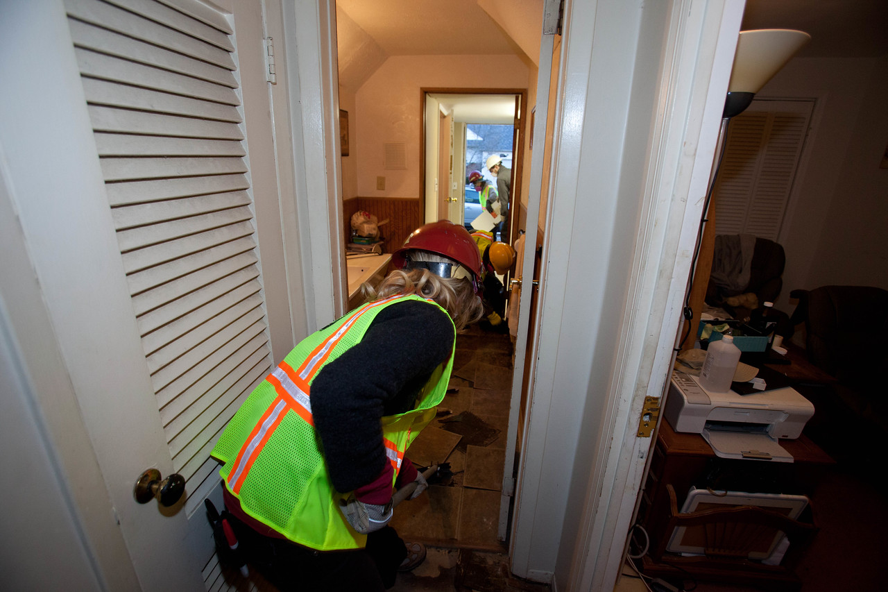 AmeriCorps member removing tile from a home damaged by hurricane Sandy in Union Beach, NJ. Corporation for National and Community Service Photo.