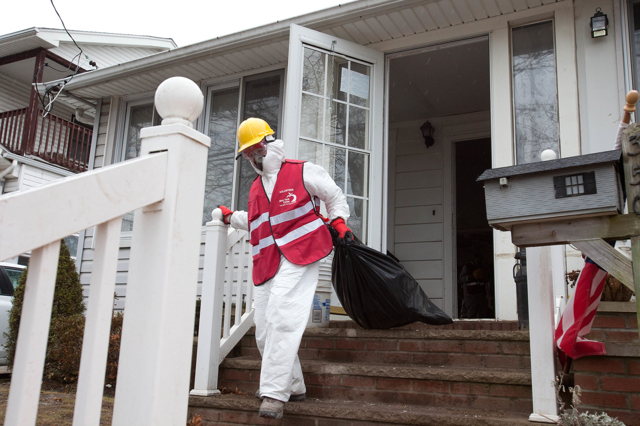 New York Cares Volunteer removing debris from a home in Belle Harbor, NY. Corporation for National and Community Service Photo.