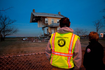 An AmeriCorps member and CNCS CEO Wendy Spencer look at a 150-year-old home in Union Beach, NJ, that was cut in half by Hurricane Sandy. Corporation for National and Community Service photo.