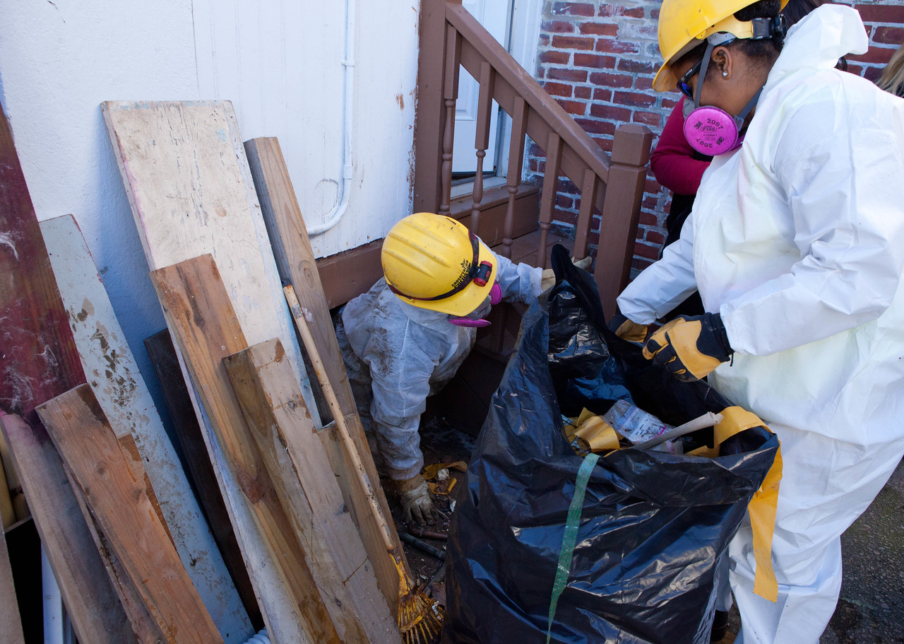 AmeriCorps members remove debris from a crawl space at a home in Atlantic City, NJ. (Corporation for National and Community Service photo)
