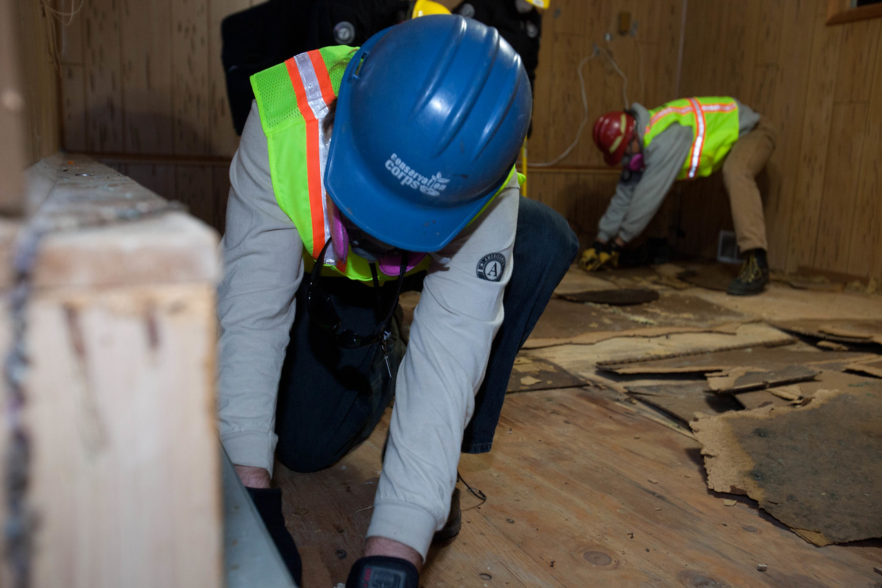 AmeriCorps members from the Washington Conservation Corps, AmeriCorps St. Louis, and Conservation Corps of Minnesota and Iowa remove flooring from a home in Union Beach, NJ, damaged by Hurricane Sandy in 2012. (Corporation for National and Community Service photo.)