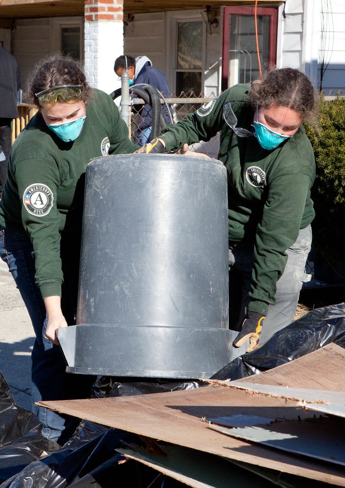 Two AmeriCorps NCCC alumni volunteering through NECHAMA empty a trash can filled with water-damaged debris while serving at a home in Atlantic City, NJ. Corporation for National and Community Service photo.