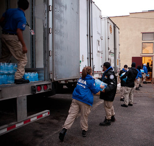 A line of FEMA Corps members help unload supply trucks in Far Rockaway, NY. (Corporation for National and Community Service photo)