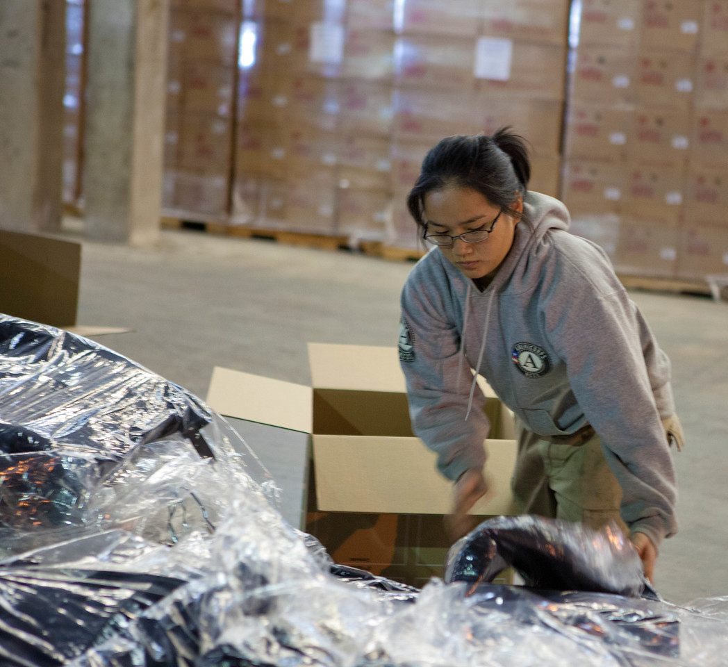 AmeriCorps member packing winter coats for hurricane survivors at the supply distribution center in Somerset, NJ in response to Hurricane Sandy. Corporation for National and Community Service Photo.