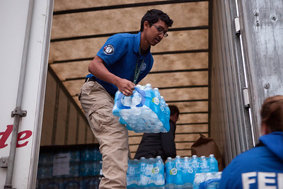 A member of FEMA Corps, a unit of AmeriCorps NCCC, unloading water from a supply truck in Far Rockaway, NY during the response to Hurricane Sandy in November 2012. Corporation for National and Community Service Photo.