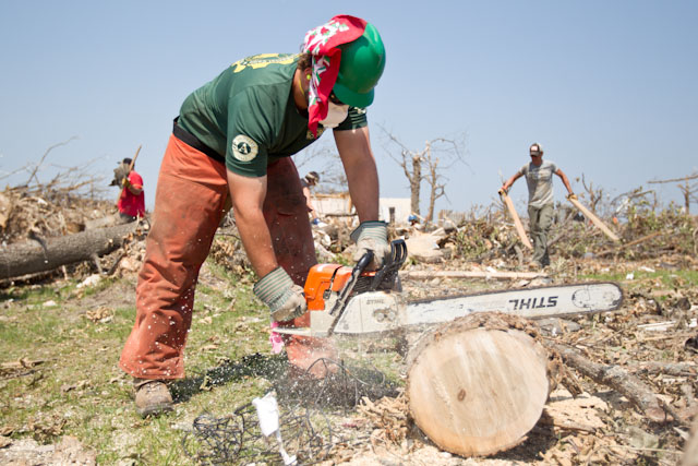 An AmeriCorps member uses a chainsaw to cut debris to help the community in Joplin, MO recover and rebuild after the devastating tornado in 2011. (Photo by Scott Julian, 2011)