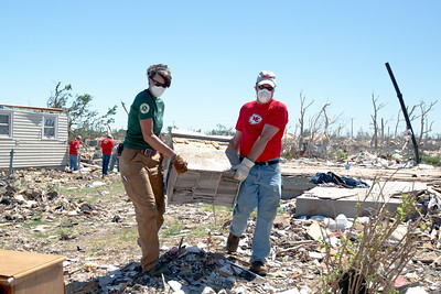 Megan Helton, an AmeriCorps member with the Texas American Youthworks Enviromental Corps Assists a Kansas City Chief player move debris. (Photo by Scott Julian, 2011)